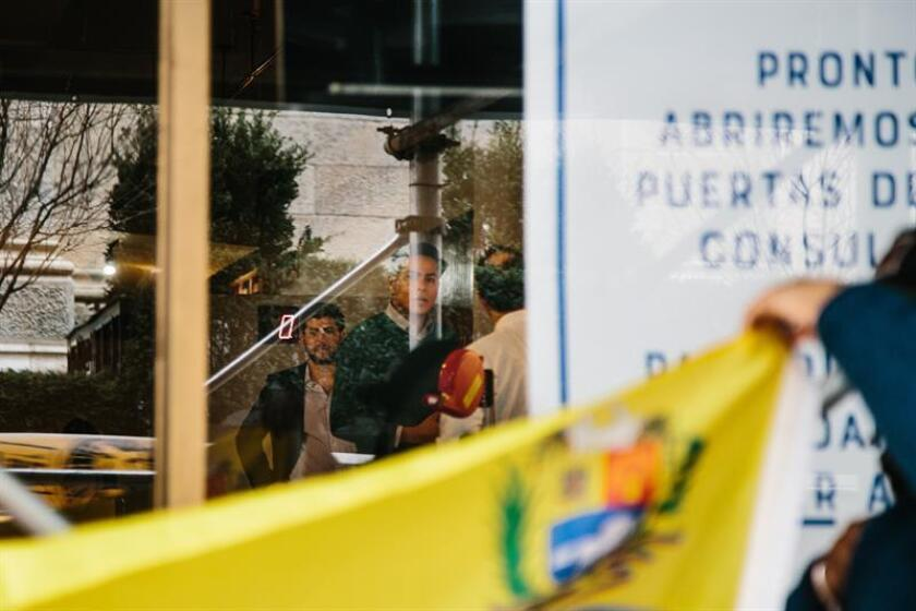 Representatives of President of the Venezuelan Parliament Juan Guaido can be seen through the glass in the Venezuelan Consulate in New York, New York, USA, 18 March 2019 after it has been announced that they have taken of control of three of the country's diplomatic properties in the United States, one of them in New York City. EPA-EFE/ALBA VIGARAY