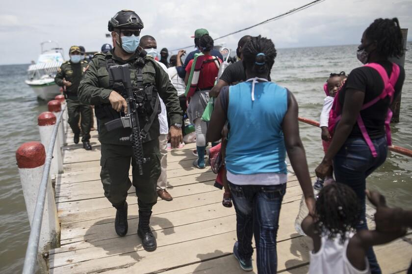 Varios policías caminan sobre el muelle el jueves 29 de julio de 2021 junto a migrantes que aguardan a abordar un bote que los llevará a Capurgana, en la frontera con Panamá, desde Necoclí, Colombia. (AP Foto/Iván Valencia)