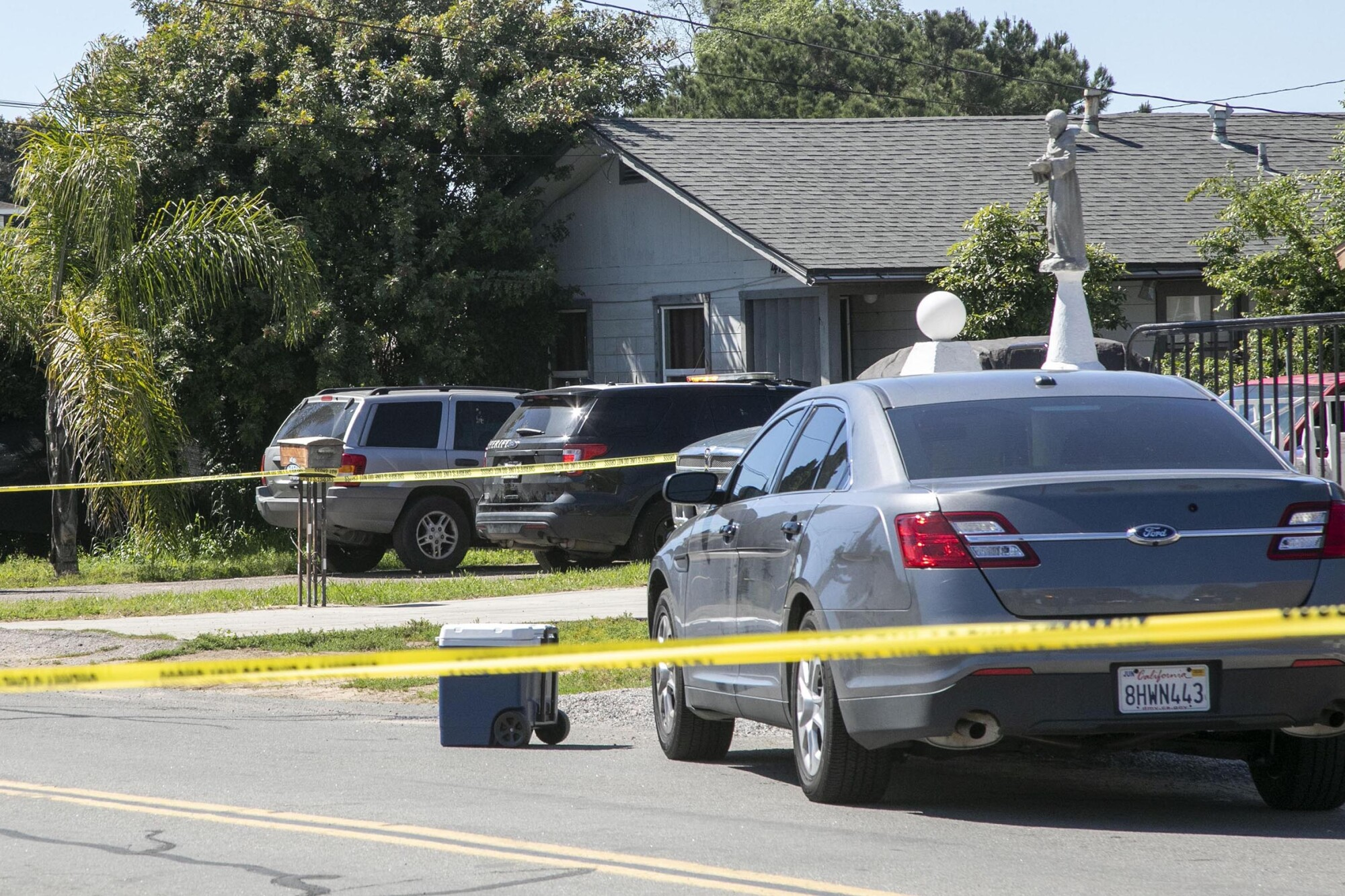 Cars parked behind police tape in front of a Lemon Grove home