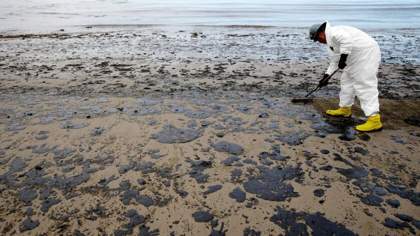 FILE - In this May 21, 2015 file photo, a worker removes oil from the sand at Refugio State Beach in