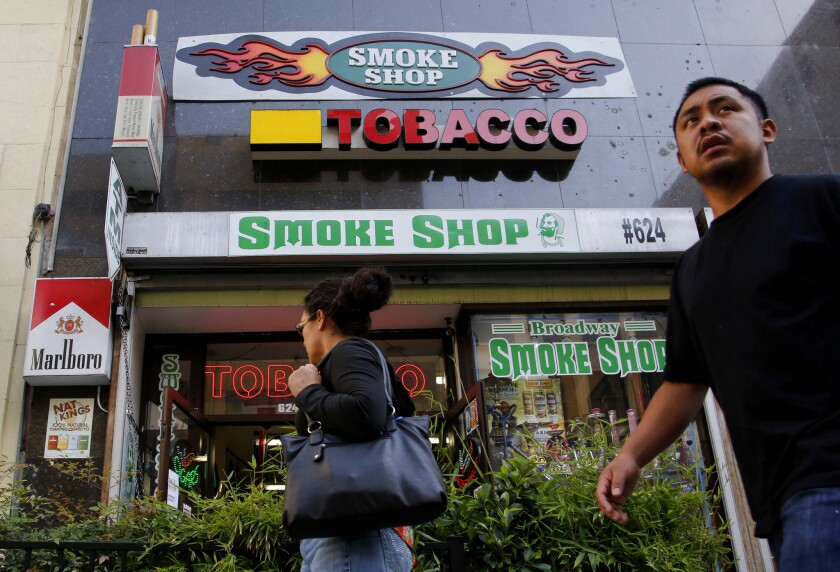 Pedestrians pass by a smoke shop on Broadway in downtown Los Angeles. Bay Area billionaire Tom Steyer has joined a a campaign proposing a ballot initiataive for a new $2-per-pack tax on cigarettes.
