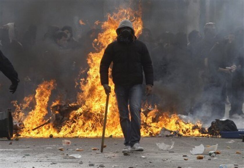 An Anarchist walks in front of burning trash during clashes in Athens on Sunday, Dec. 6, 2009. Protesters hurled rocks and burning garbage at police as violence erupted during a march to mark the first anniversary of the police shooting of a teenager, whose death sparked massive riots. Police fired tear gas at scores of hooded youths in central Athens, as several thousand demonstrators marched to commemorate the death of 15-year-old Alexandros Grigoropoulos.(AP Photo/Petros Giannakouris)