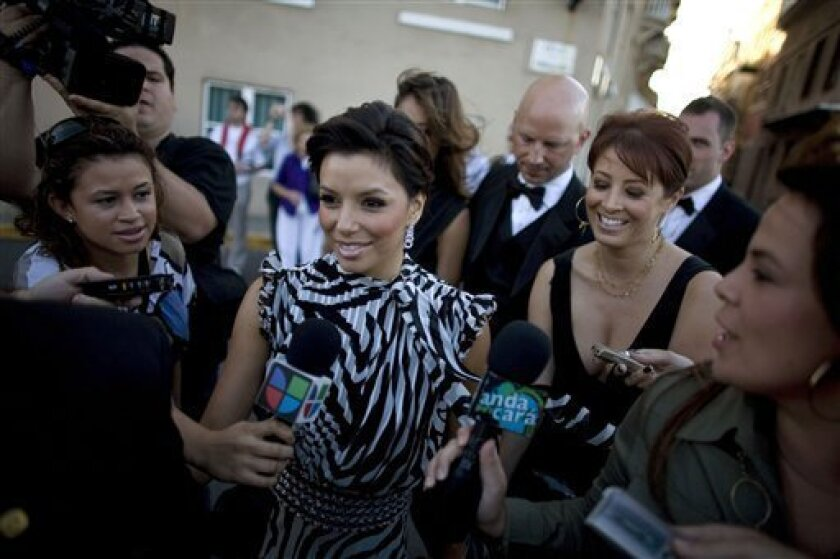 Journalists surround U.S. actress Eva Longoria, center, upon her arrival at the San Cristobal Fort, in Old San Juan, Puerto Rico, to attend the wedding of Puerto Rican actress Roselyn Sanchez and U.S. actor Eric Winter, unseen, Saturday, Nov. 29, 2008. (AP Photo/Ricardo Arduengo)