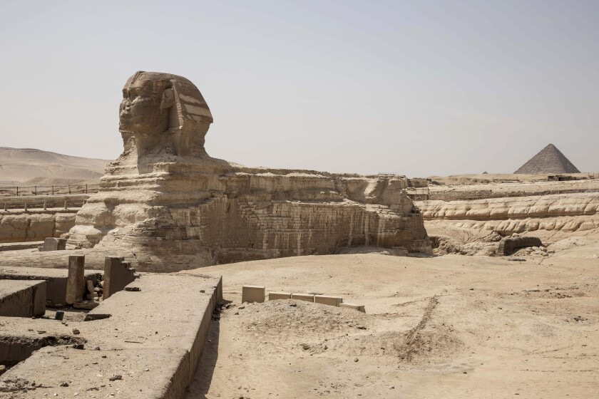 "This March 25, 2020 photo, shows the empty Sphinx complex of the Giza Pyramids in Egypt. ""Everything collapsed in a flash,"" said Sayed el-Gabri, a souvenir vendor, as he stared at the almost empty complex of Egypt's famed Giza Pyramids. It was not unexpected, but the evaporation of the stream of visitors to the ancient site was still a shock to el-Gabri and other tourism workers. He saw it coming, as the government stepped up its measures to slow the new coronavirus' spread, culminating in a ban on all international flights in and out of the country. (AP Photo/Nariman El-Mofty)"
