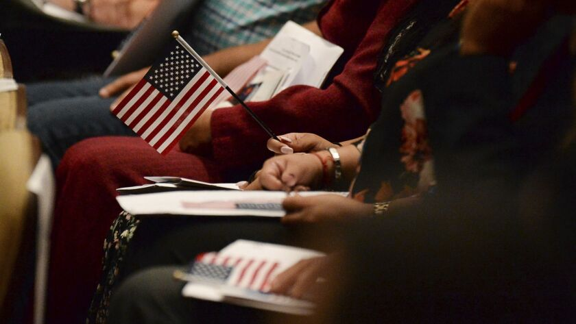 Immigrants sit at a naturalization ceremony. In the bribery case, federal officers approved applications of ineligible immigrants to become naturalized citizens and received $1,000 per immigrant, officials said.