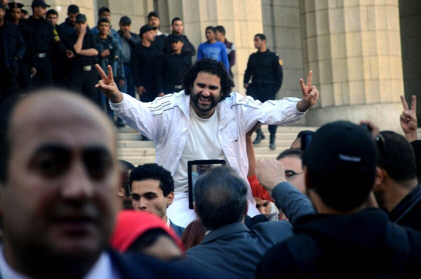 Alaa Abdel Fattah is surrounded by supporters last March after his release from detention in Cairo. Egyptian security forces arrested the prominent political activist in late November for defying a new law that tightly restricts protests in the country. On Sunday, he and 11 others were found guilty and given suspended sentences.