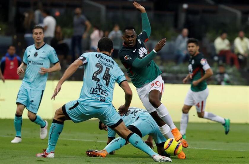 Alex Ibarra (d), del América de México, fue registrado este sábado al disputar un balón con Carlos Izquierdoz (i), del Santos Laguna, durante un partido de la jornada 17 del torneo mexicano de fútbol, en el estadio Azteca de Ciudad de México. EFE