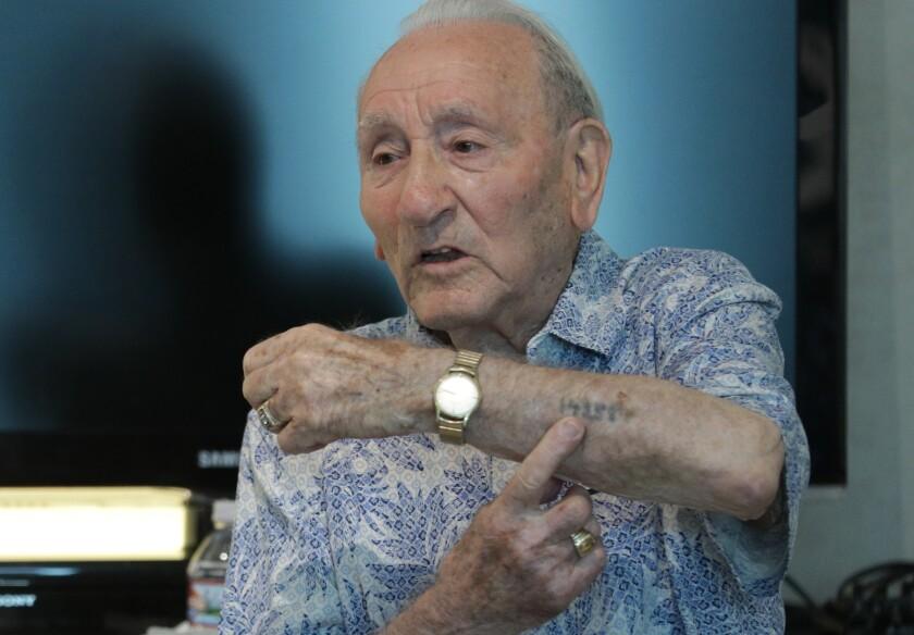 Holocaust survivor Joseph Alexander shows his identification tattoo from Auschwitz