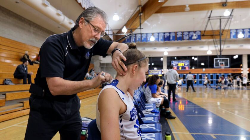 Robbie Bowers, a full-time certified athletic trainer at Rancho Bernardo High, assists athlete Annie Meggers.