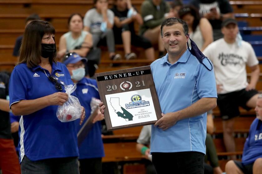 Corona del Mar High head coach Mark Alex accepts the runner-up plaque for his team.