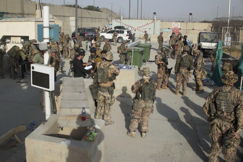 Members of the British and U.S. military help people evacuate