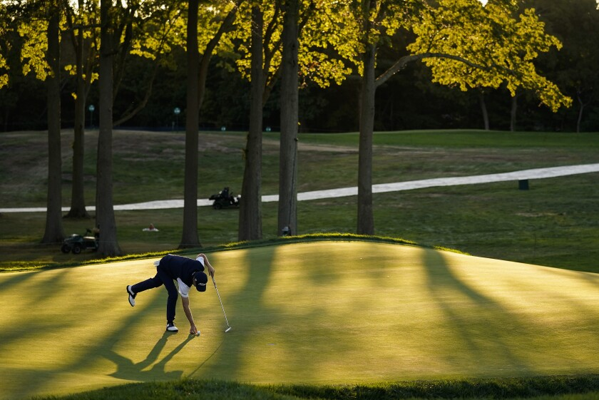 Justin Thomas, of the United States, marks his ball on the 18th green during the third round of the US Open Golf Championship, Saturday, Sept. 19, 2020, in Mamaroneck, N.Y. (AP Photo/Charles Krupa)