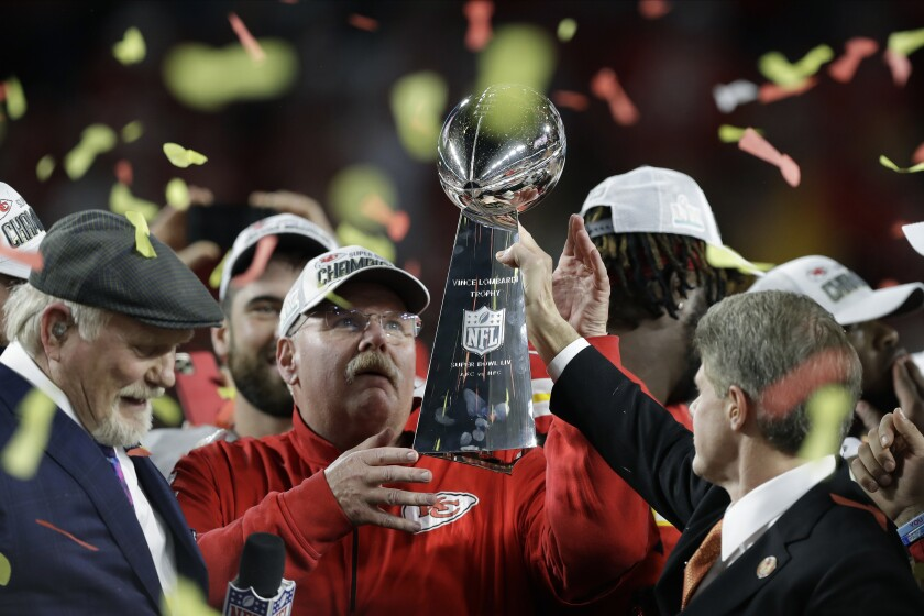 Kansas City Chiefs chairman Clark Hunt, right, hands trophy to coach Andy Reid after the Super Bowl victory against the 49ers.