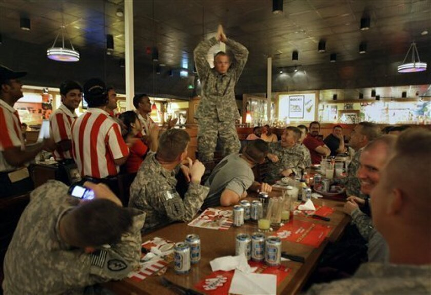 Sgt. Charles Reed, from Steam Boat, Colo., of the 715 Military Intelligence Unit, center, celebrates his 34th birthday with his colleagues and the staff at TGI Fridays restaurant on the boardwalk at Kandahar Air Force Base, Afghanistan, Monday, Sept. 6, 2010. (AP Photo/Adil Bradlow)