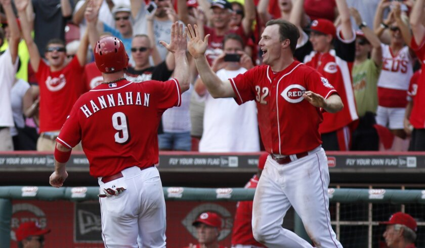 The Reds' Jay Bruce congratulates teammate Jack Hannahan after beating the Padres in 13 innings.