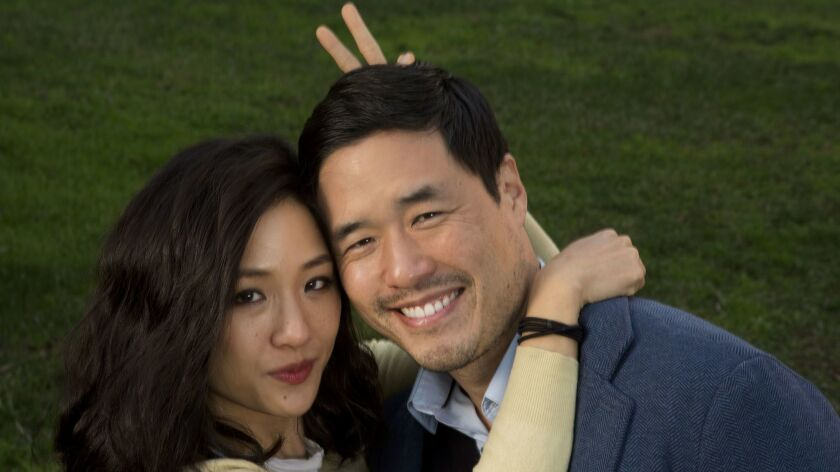 "Constance Wu and Randall Park in ""Fresh Off the Boat."" She has her arms around him and is doing bunny ears behind his head."