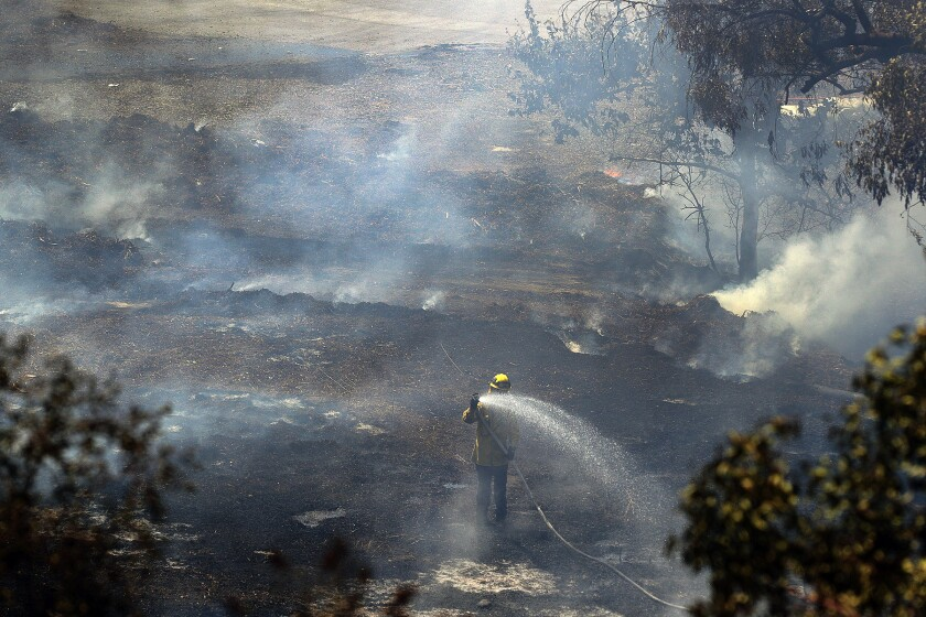 A firefighter points a hose at a hot spot in a grassy area between the 134 and 2 freeways as fire crews from Glendale and Los Angeles continue to battle a brush fire that erupted in Eagle Rock on Sunday.