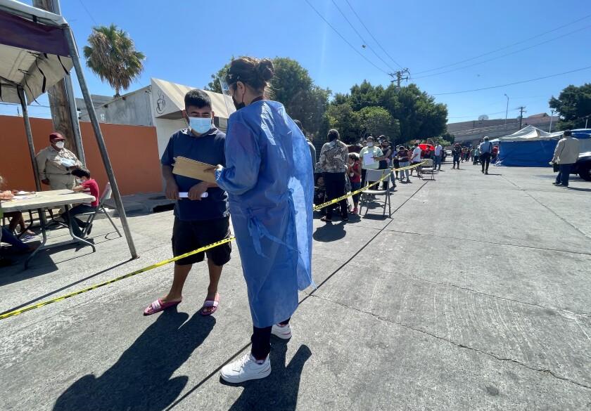 Personal de salud entrevista a migrantes antes de ser vacunados en clínica instalada en El Chaparral , en Tijuana.