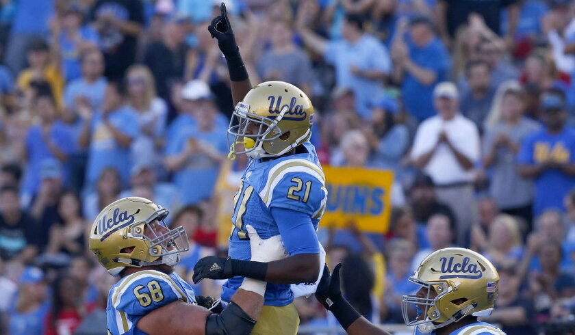 UCLA's Mossi Johnson, center, celebrates with teammates Conor McDermott, left, and Jalen Starks after scoring a touchdown Sept. 10 against the University of Nevada, Las Vegas.