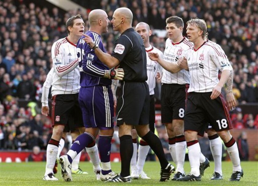 Liverpool's Pepe Reina, second left, and Daniel Agger, left, argue with referee Howard Webb after he awarded a penalty to Manchester United during their third round FA Cup soccer match at Old Trafford, Manchester, England, Sunday Jan. 9, 2011. (AP Photo/Jon Super)