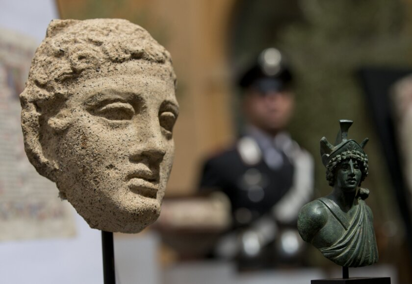 A third century B.C. terracotta head, left, and a second century Roman bronze figure representing Mars, are shown during a press conference in Rome, Tuesday, May 26, 2015. The United States has returned 25 artifacts that were looted from Italy, including Etruscan vases, 1st century frescoes and pre