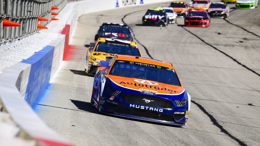 Brad Keselowski leads a row of cars as they come through the front stretch during a Monster Energy N