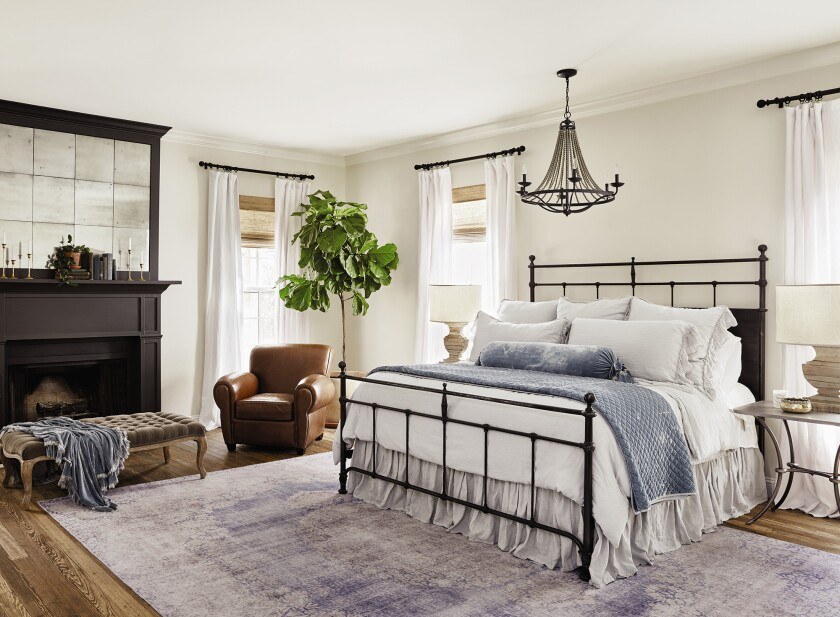 Draperies are hung inches above window frames and the rug pulls everything together in Chip and Joanna Gaines' Texas farmhouse bedroom.