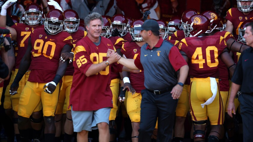 Will Ferrell, left, and USC Coach Steve Sarkisian lead the Trojans out of the Coliseum tunnel before their Pac-12 Conference game against Stanford on Saturday.