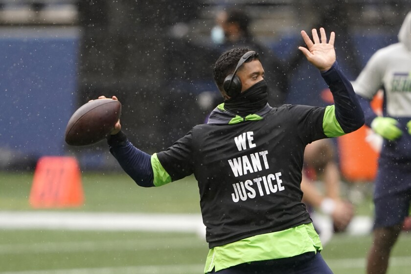 Seattle Seahawks quarterback Russell Wilson warms-up in a light rain before an NFL football game against the Minnesota Vikings, Sunday, Oct. 11, 2020, in Seattle. (AP Photo/Ted S. Warren)