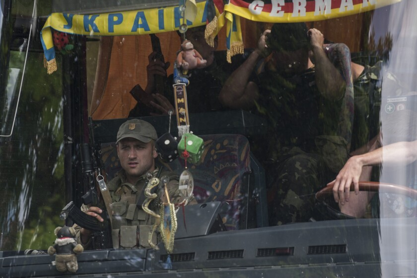 Ukrainian troops photographed through a bus window leave a place of battle in Mariupol, eastern Ukraine, on Friday.