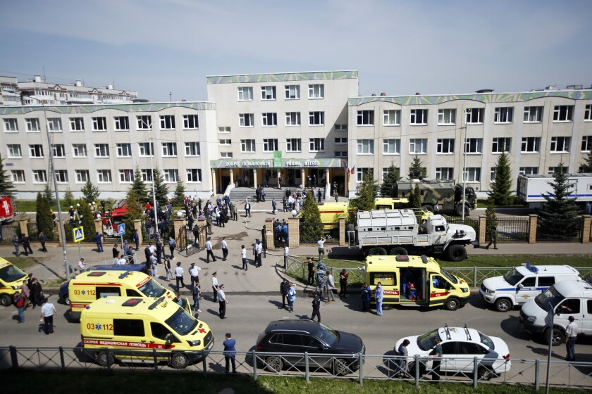 Ambulances and police cars are parked at a school after the shooting in Kazan, Russia