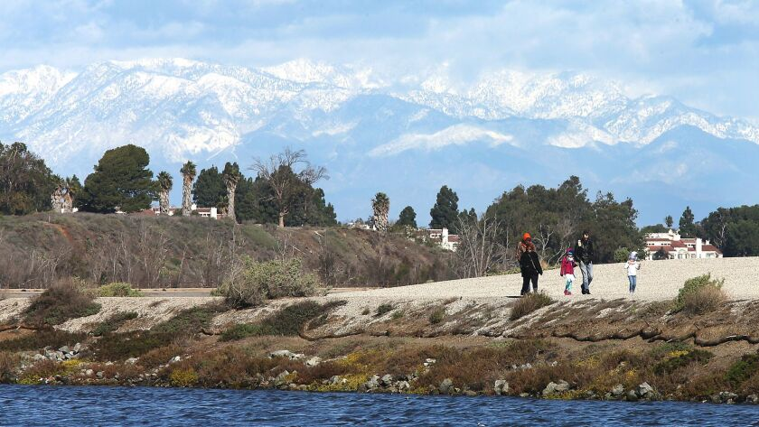 Visitors to the Bolsa Chica Wetlands enjoy a chilly, blustery day beneath puffy clouds and a backdrop of the snow-covered San Gabriel Mountains.