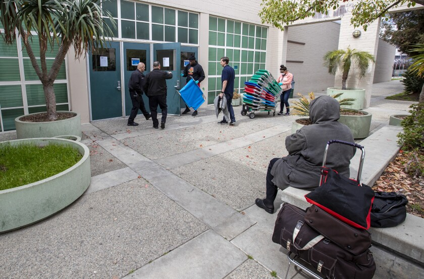 A homeless woman waits as city workers and volunteers with the Salvation Army set up cots at Westwood Recreation Center, which is now doubling as a shelter because of the coronavirus.