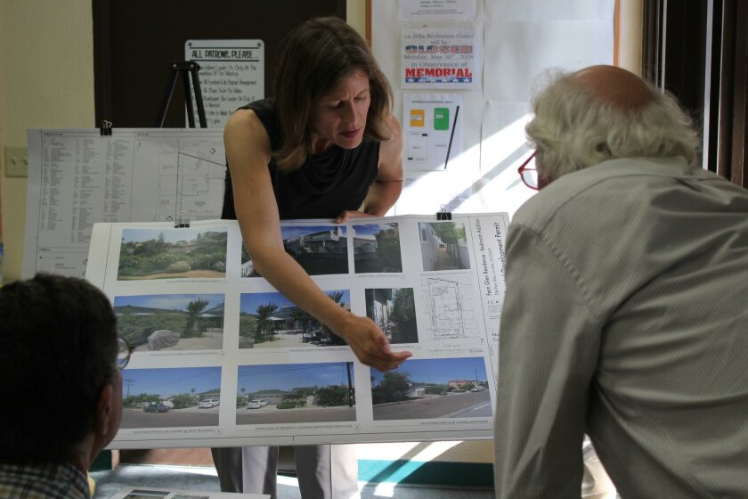 Applicant Jennifer Charles shows pictures of the Fern Glen house to DPR members Mike Costello and Matthew Welsh.