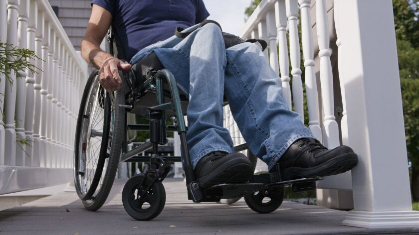 Man with spinal cord injury in a wheelchair on the top of home access ramp
