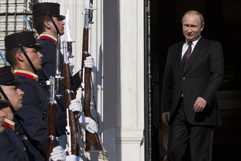 Russian President Vladimir Putin stands at the entrance of the Greek prime minister's official residence in Athens, Friday, May 27, 2016. On his first trip to a European Union country this year, Putin sharply criticized western policy toward Moscow and called a newly-expanded U.S. missile defense s