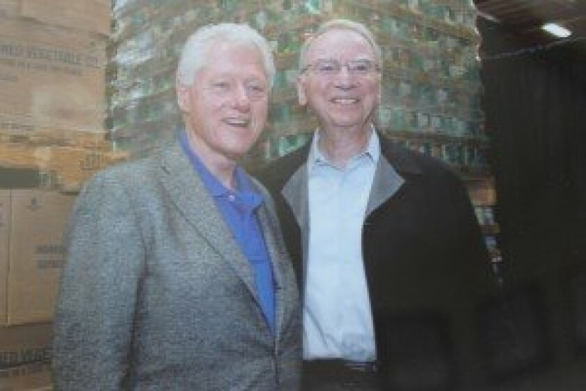 This photo of Irwin Jacobs and President Bill Clinton at the San Diego Food Bank is one of many adorning the desk of Jacobs' home office.