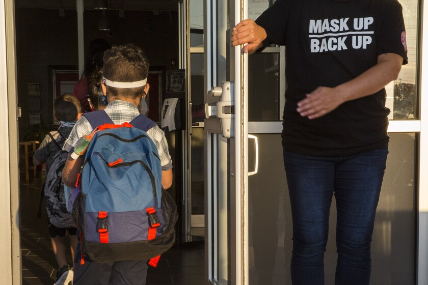 A staff member holds the door open for children on the first day of school in New Braunfels, Texas.