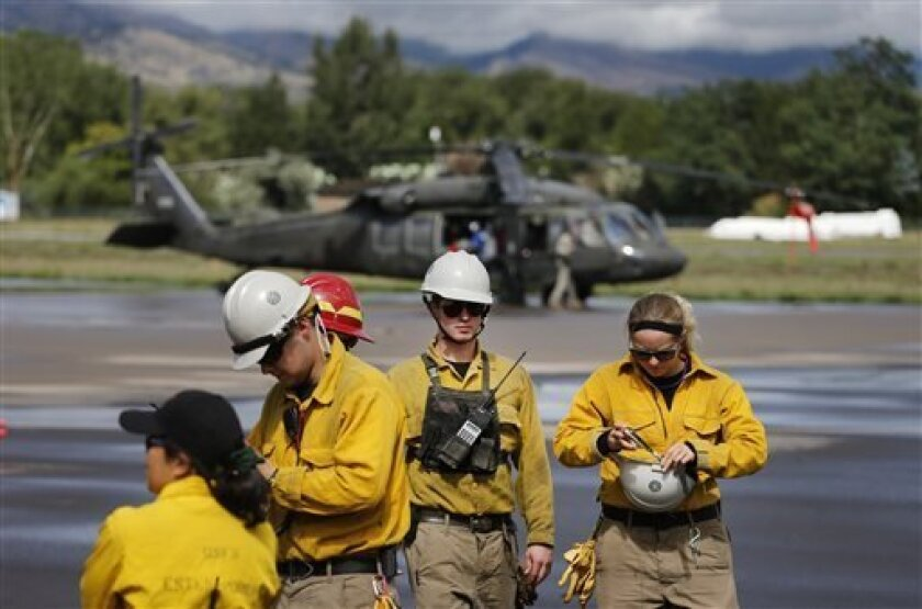 A team from Rocky Mountain Rescue prepares to depart on a mountain flood rescue mission flown by the National Guard, in Boulder, Colo., Friday Sept. 13, 2013. Flash flooding in Colorado has left at least three people reportedly dead and the widespread high waters have hampered emergency workers' access to affected communities as heavy rains hammered northern Colorado. (AP Photo/Brennan Linsley)