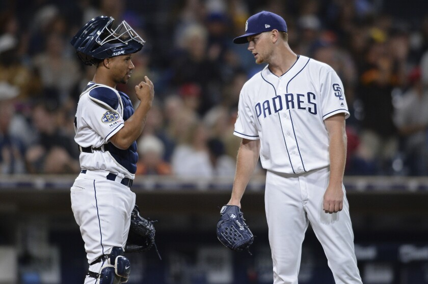 Padres catcher Francisco Mejia, left, and Eric Lauer have a discussion during the fourth inning of a game against the Colorado Rockies on Thursday.