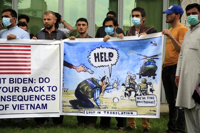Afghan interpreters hold banners, including one with a political cartoon showing the U.S. military abandoning them
