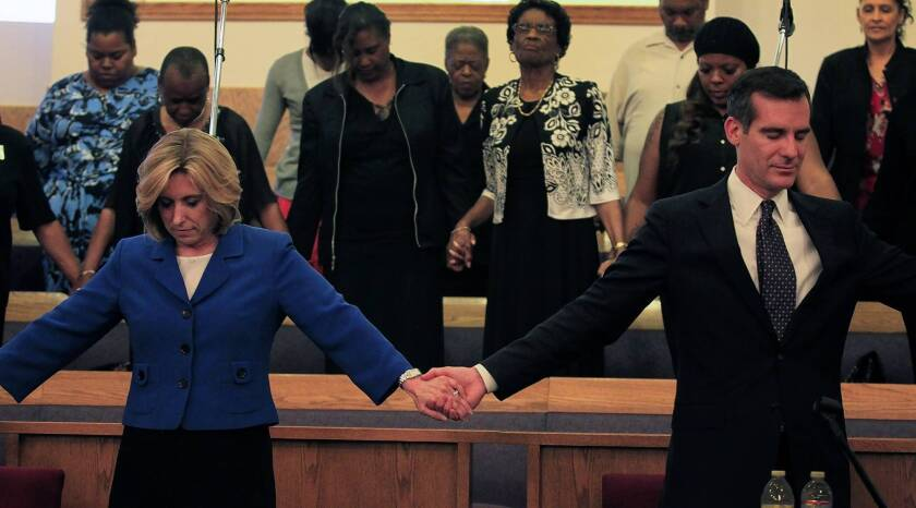 Wendy Greuel, left, and Eric Garcetti join hands in prayer after their candidates forum at Macedonia Baptist Church in Watts.