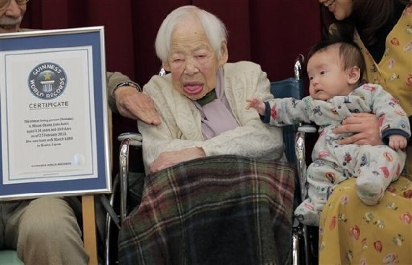 Japan's 114-year-old Misao Okawa, center,  poses with her 2-month-old great-grandson Hibiki Okawa  along with the Guinness World Records certificate at a nursing home in Osaka, western Japan, Wednesday, Feb. 27, 2013.  Okawa has been recognized as the world's oldest woman by Guinness World Records