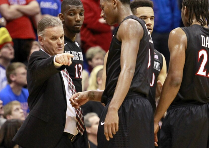 San Diego State assistant coach Brian Dutcher gives some direction to his players during a game against Kansas last month.