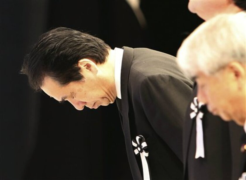 Former Japanese Prime Minister Naoto Kan bows to the altar during the national memorial service for the victims of the March 11, 2011, earthquake and tsunami in Tokyo Sunday, March 11, 2012. Through silence and prayers, people across Japan on Sunday remembered the massive disaster that struck the n