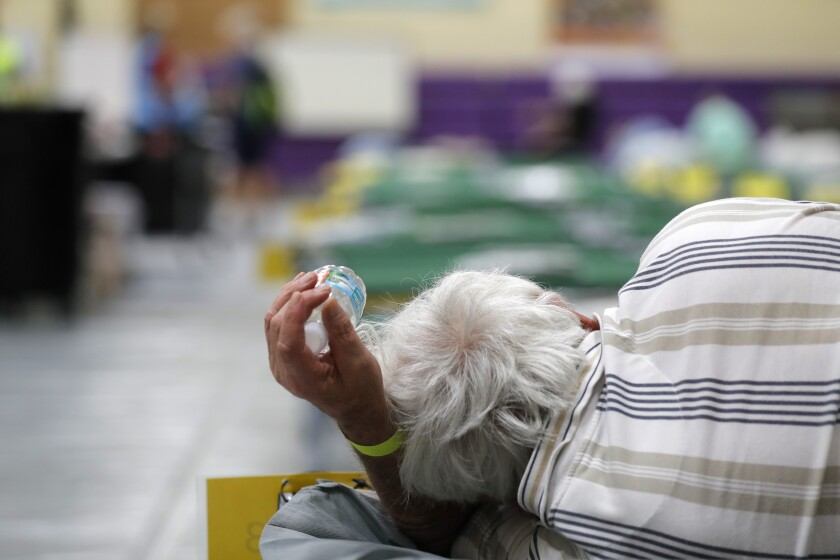 An evacuee lies on a cot at a shelter in Stuart, Fla., in September 2019 before Hurricane Dorian.
