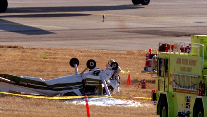 ME.Crash.152.0623.CC––John Wayne Airport––A 757 taxis by a Cessna 152 that had crashed on the grass