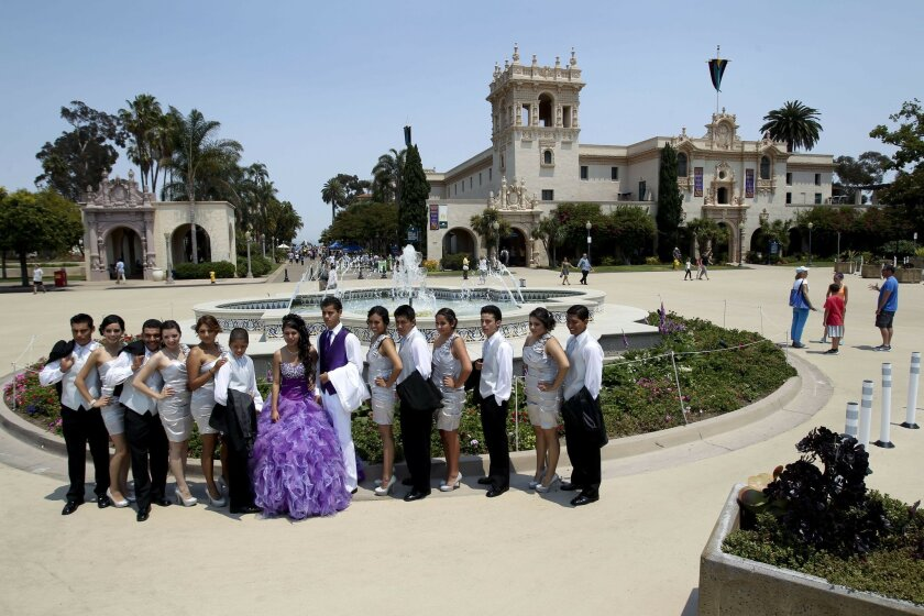 Lucy Cardenas, center, from San Marcos, from San Marcos, poses for pictures with her friends as they celebrate for 15th birthday with a quinceanera party at the Plaza de Panama at Balboa Park in San Diego.