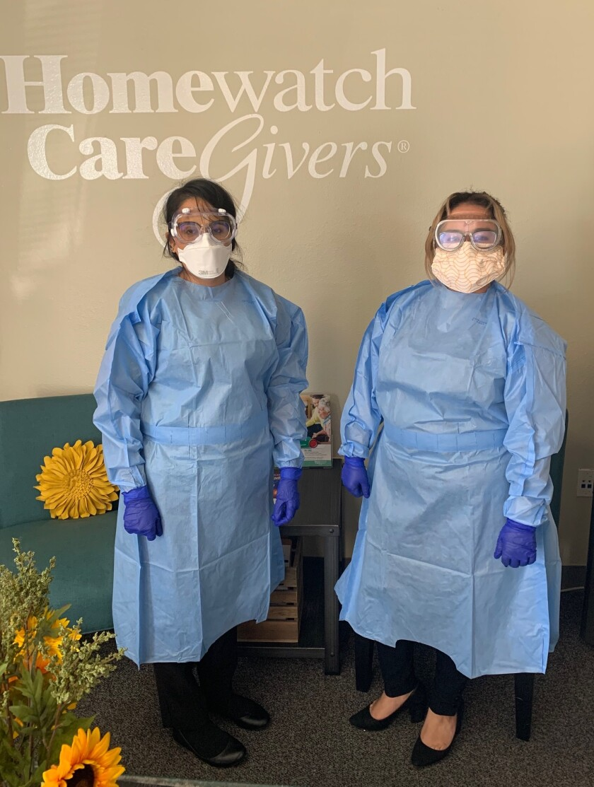Two Homewatch Caregivers staff members stand ready in their personal protective equipment.
