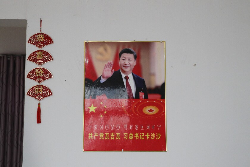 A poster showing an image of Chinese President Xi Jinping is displayed on a wall at a home of members of the Yi minority group in Xujiashan village in Ganluo County, southwest China's Sichuan province on Sept. 10, 2020. Communist Party Xi's smiling visage looks down from the walls of virtually every home inhabited by members of the Yi minority group in a remote corner of China's Sichuan province. Xi has replaced former leader Mao Zedong for pride of place in new brick and concrete homes built to replace crumbling traditional structures in Sichuan's Liangshan Yi Autonomous Prefecture, which his home to about 2 million members of the group. (AP Photo/Andy Wong)